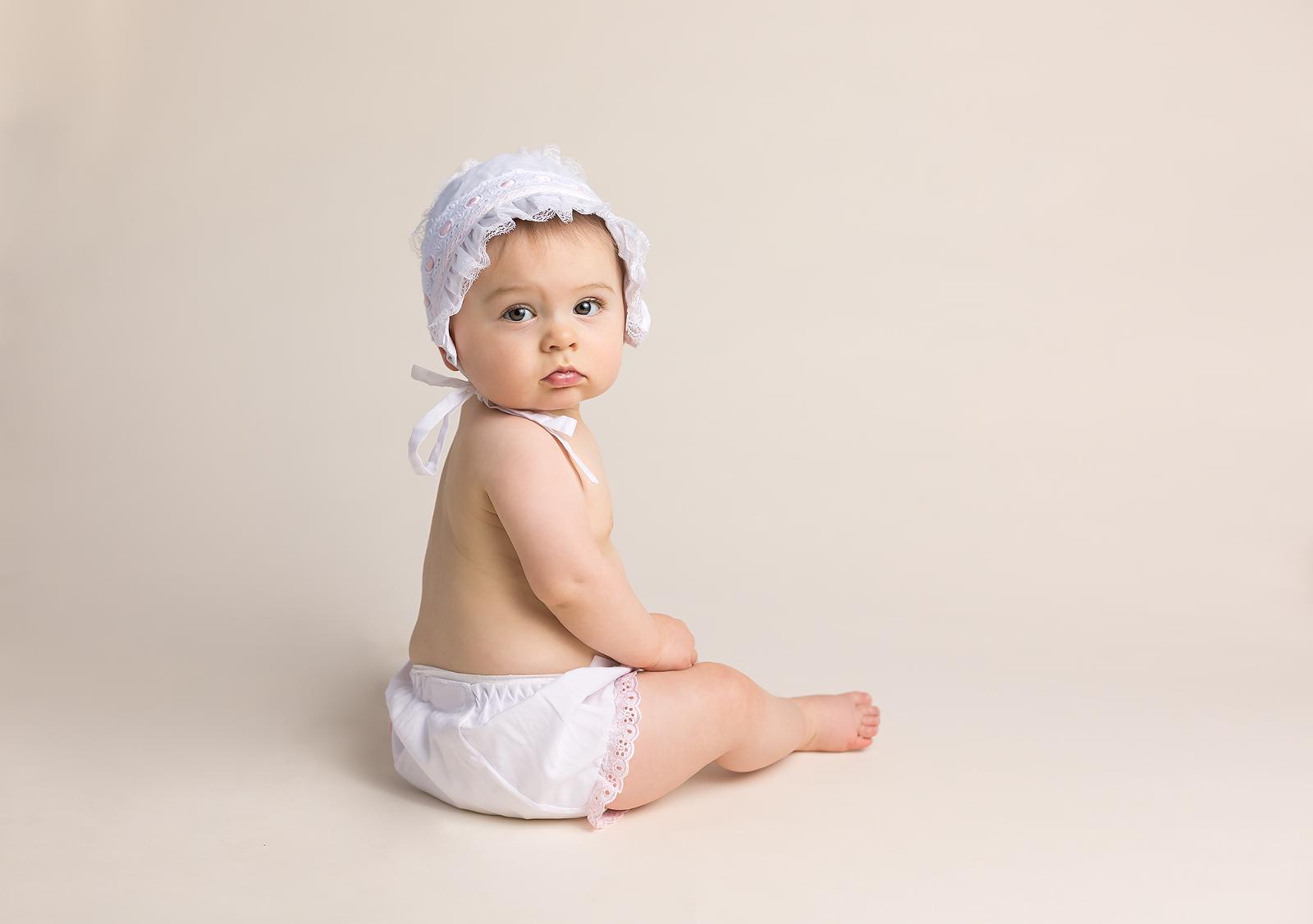 girl in white dress wearing a bonnet